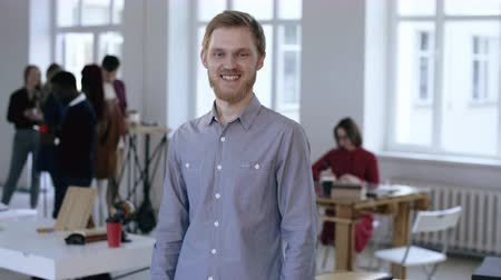 haklar : Portrait of young confident successful European male executive manager looking at camera smiling in modern light office.