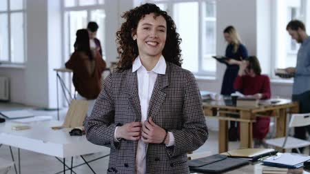 feminism : Medium portrait of young Caucasian business woman with curly hair, formal suit smiling happy at camera at modern office. Stock Footage