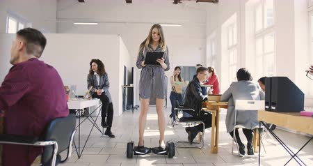 bossy : Young confident serious blonde business woman in dress riding electric gyroscooter in modern loft multiethnic office.