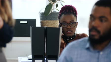 feminism : Young professional African female boss is stressed talking on the phone sitting at table in multiethnic modern office.