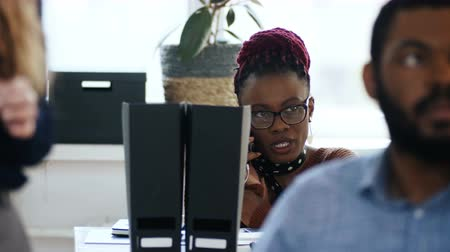 femminismo : Young stressed African female company manager in eyeglasses talking on the phone at table in multiethnic modern office.