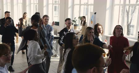 doorbraak : Happy multi ethnic business people group dancing together celebrating holidays at modern light office, workplace party. Stockvideo