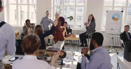 motivováni : Fun happy African business woman doing crazy celebration dance at modern loft office workplace, colleagues share success