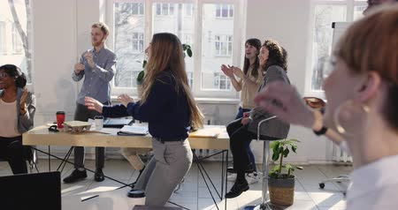 motive : Beautiful happy fun blonde business woman dancing, celebrating success with colleagues at modern multiethnic office.