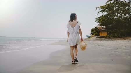 strohoed : Slow motion back view happy young attractive traveler woman walking slowly at exotic tropical ocean beach slow motion. Stockvideo