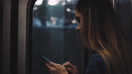 rueda de chicago : Young brunette woman going somewhere in moving subway train. Girl using smartphone standing near the window on sunset. Archivo de Video