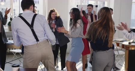 motivováni : Victory celebration at healthy modern workplace. Excited young happy female boss dancing with multiethnic colleagues. Dostupné videozáznamy