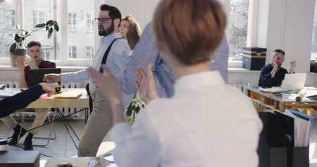 motivados : Fun young successful businessman sharing big career success celebration with coworkers doing crazy dance walk at office.