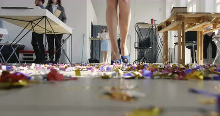 bossy : Low angle legs of beautiful woman leader walking on confetti covered floor at modern office workplace after party.
