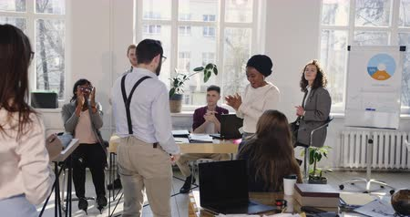 turban : Happy African business woman in ethnic turban doing fun crazy success celebration dance at modern loft office workplace. Stock Footage