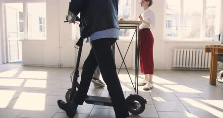 healthy workplace : Young stylish businessman riding electric scooter in modern trendy office, talking to colleagues. Multiethnic workplace. Stock Footage