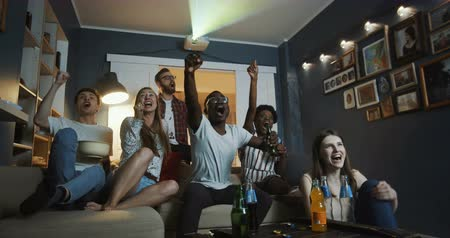 juntar : Excited young happy multiethnic friends get emotional and shout watching sports on TV together at home slow motion.