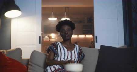 novela : Happy young millennial African woman smiles watching TV soap opera series at home on the couch with snacks slow motion. Stock Footage