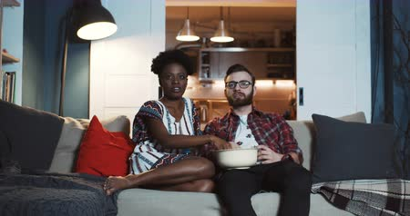 family watching tv : Happy young Caucasian man and African woman sit at home watching dramatic movie together, eating popcorn slow motion.