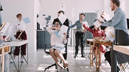 carreira : Happy young business woman celebrating success with office colleagues throwing paper in air slow motion. Stock Footage