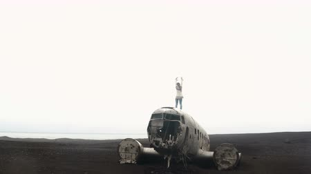 dc : Freedom: back view of young woman in lopapeysa standing on the top of breaker DC-3 BMC plane on black beach in Iceland. Stock Footage