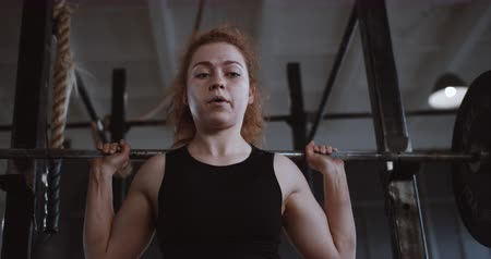 overcome : Young beautiful red haired athletic woman straining hard lifting heavy barbell in large professional gym slow motion.