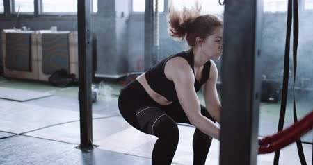 aspire : Young beautiful athletic red haired woman working out with battle rope, functional training in large gym slow motion.