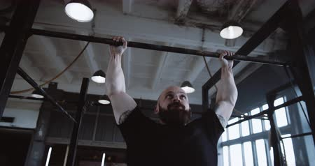 role model : Athletic young strong handsome Caucasian man doing pull-ups during functional workout in large gym slow motion.