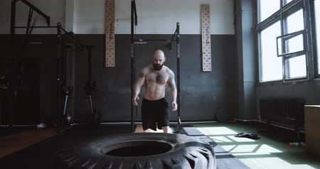 overcome : Extreme functional training, athletic young Caucasian man lifting giant tire during workout in large gym slow motion. Stock Footage