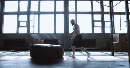 role model : Extreme workout, muscular young shirtless man exercising with giant tire during training in gym side view slow motion. Stock Footage
