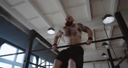 ağır çekimli : Athletic young muscular Caucasian man doing extreme pull-up exercises during functional workout in large gym slow motion Stok Video