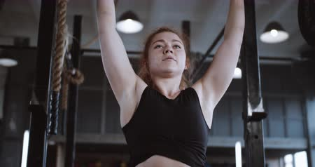 aspire : Close-up young beautiful red haired athletic woman lifting heavy crossbar, extreme workout in large professional gym.