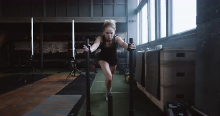 aspire : Motivation concept, young athletic blonde woman pushing heavy training sled towards camera training in gym slow motion.
