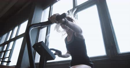 aspire : Young beautiful athletic blonde woman working out on stationary gym bike machine with wind in hair from fan slow motion.