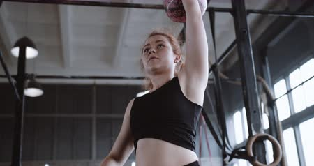 aspire : Young athletic red haired professional athlete woman lifting kettlebell weight in large atmospheric gym slow motion.