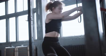 aspire : Young determined athletic red haired woman exercising with battle ropes, training in large atmospheric gym slow motion.