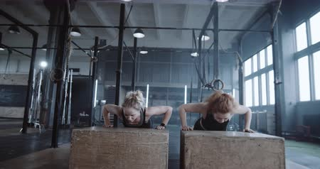 feminism : Happy beautiful young blonde woman working out together with personal female coach in big gym doing push-ups slow motion