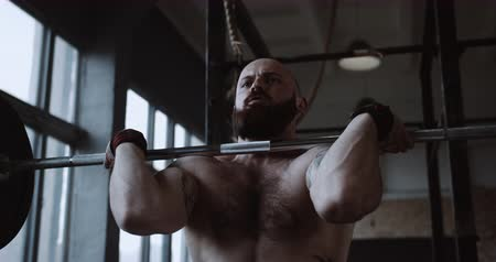 role model : Camera pans up on young athletic Caucasian bearded man lifting heavy weight barbell in large gym hall slow motion.