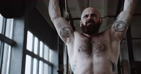 aspire : Close-up young Caucasian athlete man lifting heavy barbell in large hardcore gym hall. Ambition and challenge concept. Stock Footage