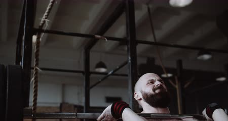 role model : Close-up young muscular Caucasian sportsman exercising with heavy weight crossbar in large hardcore gym slow motion.