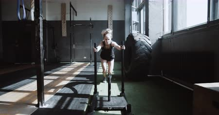role model : Young beautiful athletic Caucasian woman pushing training sled towards camera, exercising in hardcore gym slow motion. Stock Footage