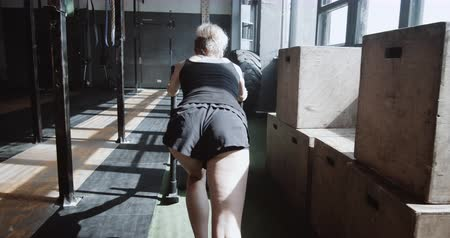 герой : Overcoming difficulties. Back view young athletic woman pushing training sled exercising in large empty gym slow motion.