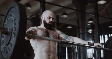 aspire : Close-up slow motion shot of young Caucasian man lifting crossbar in large gym hall, extreme heavy weight training. Stock Footage