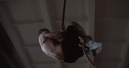 role model : Young muscular athletic Caucasian man climbing rope, doing hardcore functional workout training in large gym slow motion