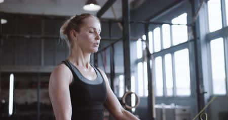 aspire : Close-up young athletic blonde woman working out with jump rope, tired and sweaty in big atmospheric gym slow motion. Stock Footage