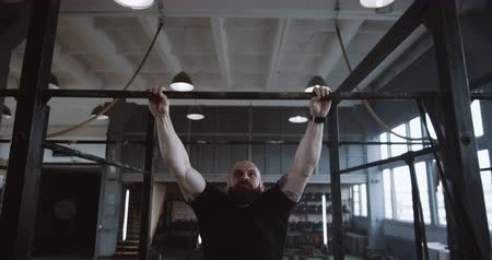 szerep : Young handsome muscular Caucasian man doing pull-ups, jumping off to rest during extreme workout in gym slow motion.