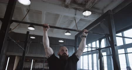 role model : Athletic young Caucasian man doing pull-up exercises during functional workout in large atmospheric gym slow motion.