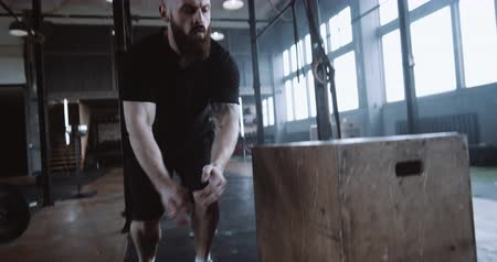 overcome : Young tough athletic Caucasian man doing functional workout in large gym, jumping on and off big block slow motion.