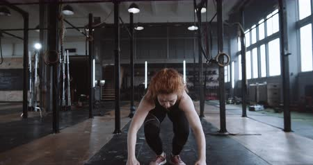 role model : Young beautiful red haired Caucasian female athlete doing burpee exercises during functional workout in gym slow motion.