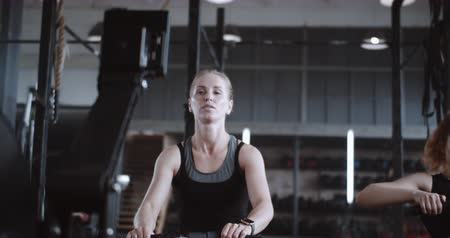 aspire : Active and healthy lifestyle, young beautiful happy blonde woman working out on rowing machine in gym slow motion.