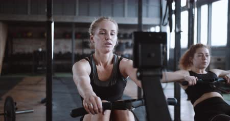 overcome : Healthy lifestyle. Young beautiful happy blonde woman works out on rowing machine in gym with personal coach slow motion