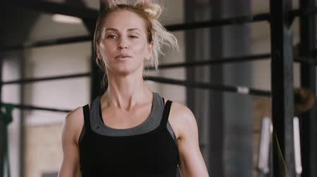 overcome : Close-up smiling young blonde woman exercising with jumping rope in gym slow motion, living active healthy lifestyle. Stock Footage