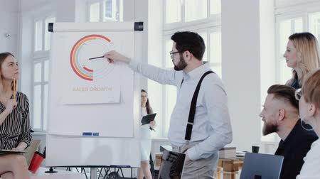 directional : Happy young boss businessman explaining sales diagram on flipchart at modern office seminar event slow motion