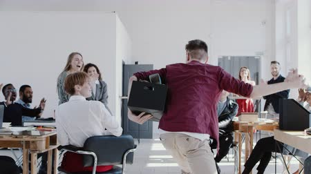 licenziato : Camera follows happy successful male manager giving high fives to office team colleagues with a box slow motion