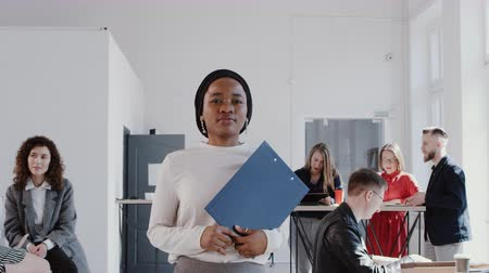 aktatáska : Happy beautiful successful black business woman walking along modern office looking at camera slow motion